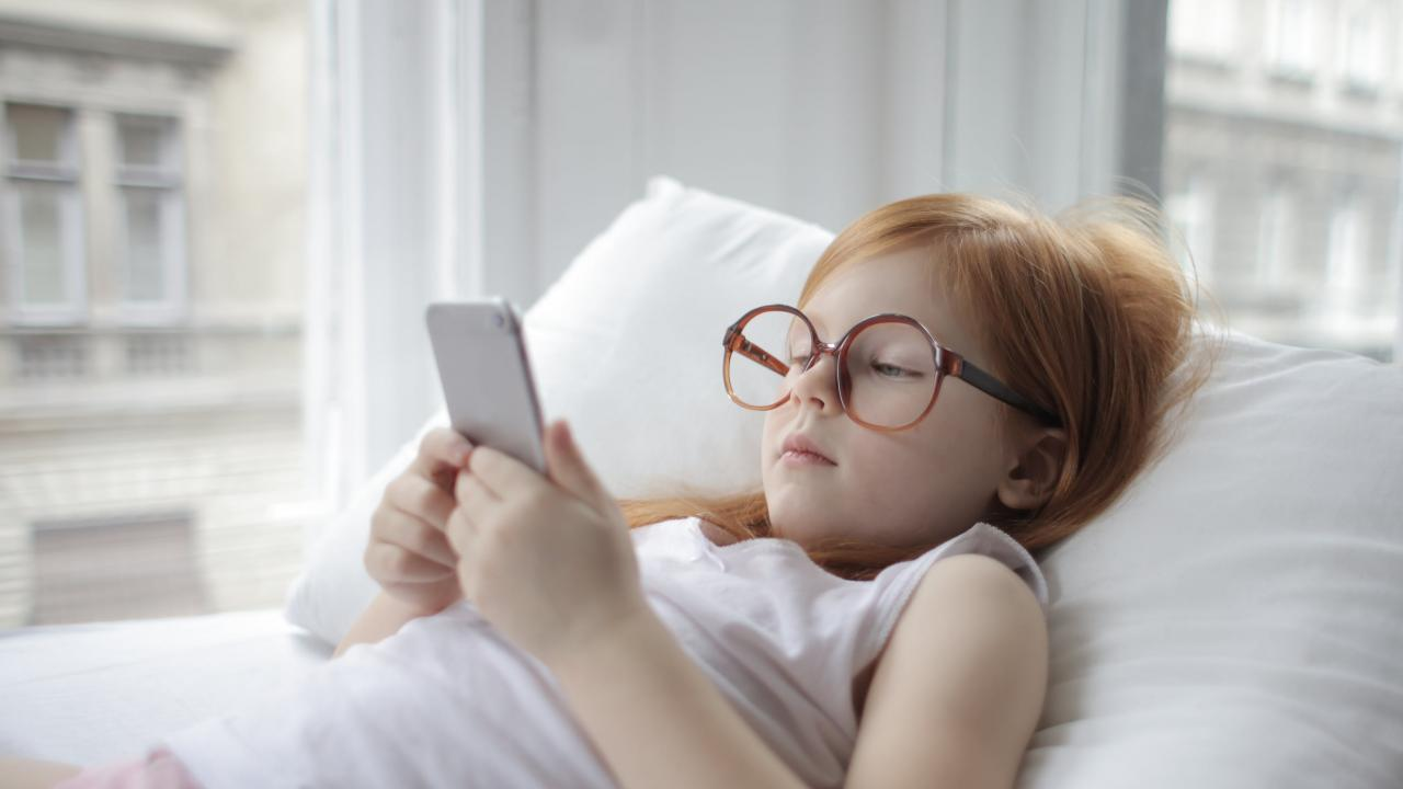 A young girl uses a smart phone.